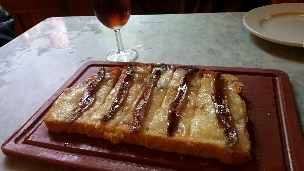 Country bread with cheese and anchovies.  With a side of sherry.