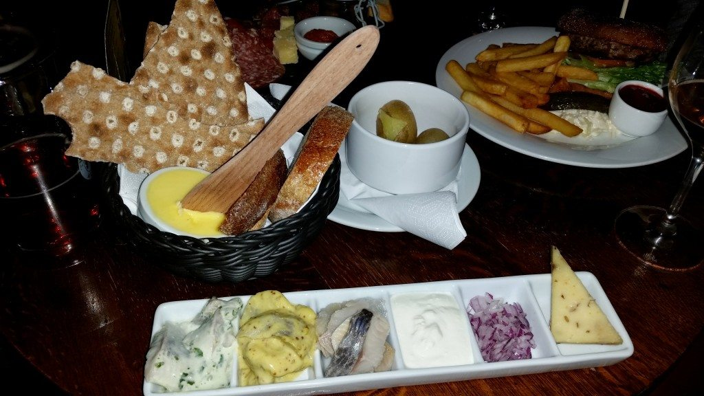 Three types of pickled herring served with crisp bread, sour cream, onions and potatoes.