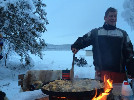 Tomas cooking our reindeer firetop during a break from snowmobiling.