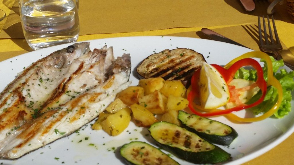 Grilled fish and veggies in a sunny square in Venice.